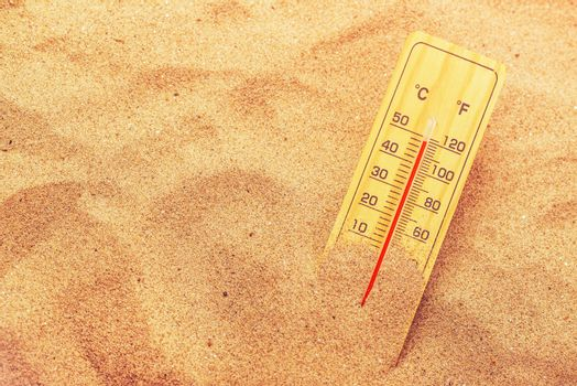 Thermometer on extremely warm desert sand