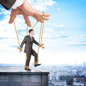 Businessman hanging on strings like marionette