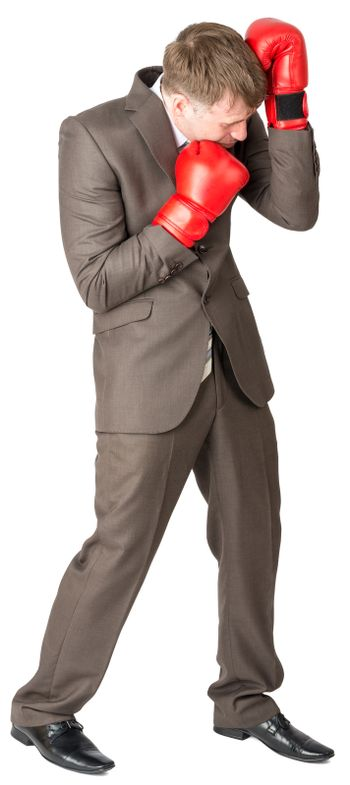 Businessman with boxing gloves defending