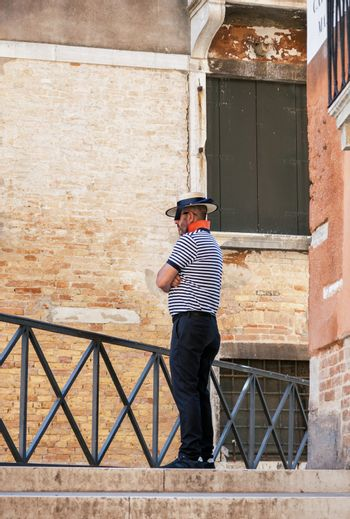 VENICE, ITALY - MAY 27, 2015: Gondolier in traditional uniform standing lonely and waiting for tourists on the street of Venice, Italy