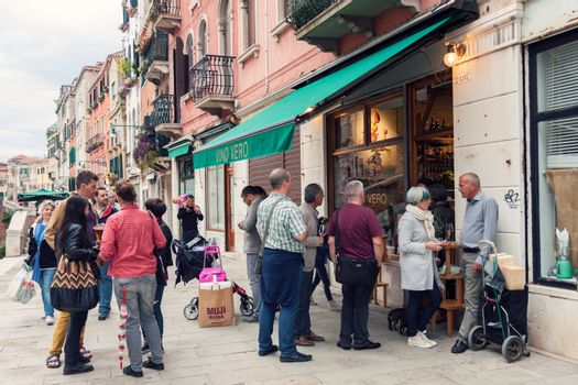 VENICE, ITALY - MAY 27, 2015: Crowd of people drinking and talking on the street outside wine bar in Venice, Italy