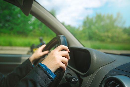 Female hands gripping car steering wheel