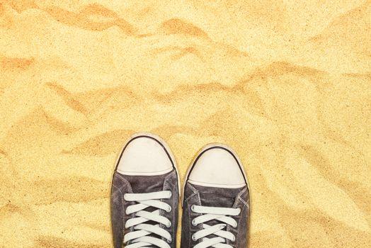 Feet in sneakers standing on war desert sand
