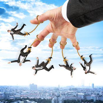 Businessmen hanging on strings like marionette