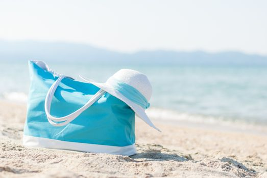 Turquoise bag and white hat on the beach.