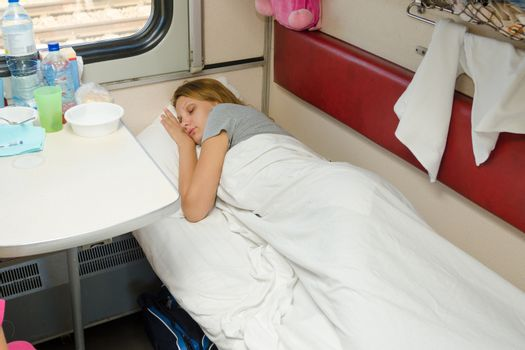 Girl sleeping in a train compartment on the lower second-class place car