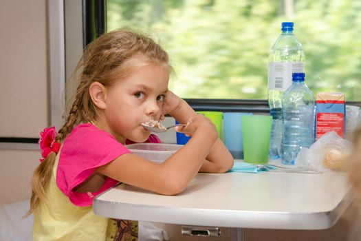 A six-year girl in a train sitting at the table on the lower place in the second-class compartment of the car and eats porridge spoon