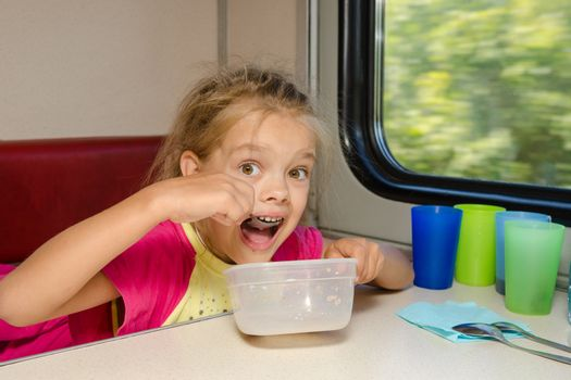 The girl on the train sits at a table on the lower place in the second-class compartment of the car and eats it with relish spoon