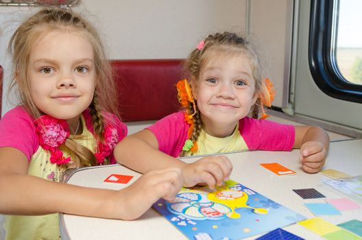 Two little sisters in the train of fun playing at the table at the lower place in the second-class compartment wagon