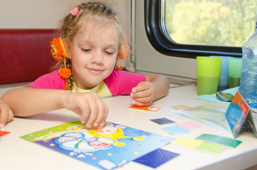 A small child in a train of fun playing at the table at the lower place in the second-class compartment wagon