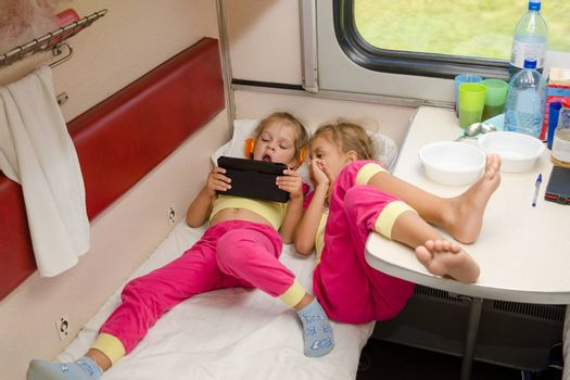 Two little girls lie on the train with his feet on the lower second-class place car in the same pajamas and looking at tablet