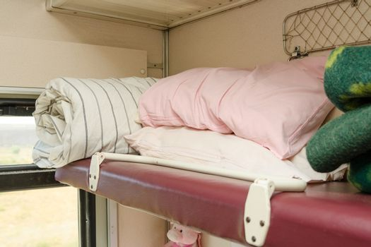 The top shelf in the second-class compartment of the train wagon with bedding