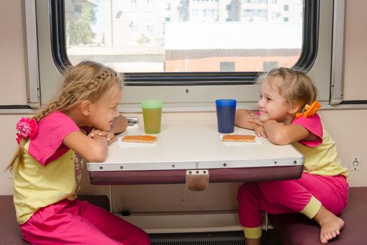 Two little girls with a happy face looking at each other on the train sitting at the table on outboard second-class carriage