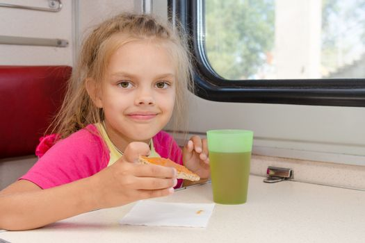 Six-year girl drinking tea with a sandwich on the train at the table on outboard second-class carriage