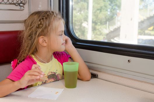 Six-year girl sitting on the train at the table on outboard second-class carriage and enthusiastically looking out the window