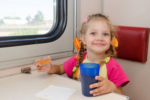 Little girl with a happy face drink tea with a sandwich on the train at the table on outboard second-class carriage