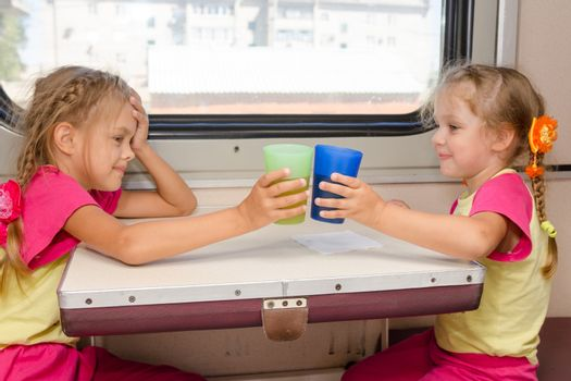 Two little sisters in identical pajamas drinking tea in the train at the table on outboard second-class carriage