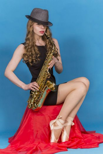 a girl and a saxophone on a blue background in the Studio