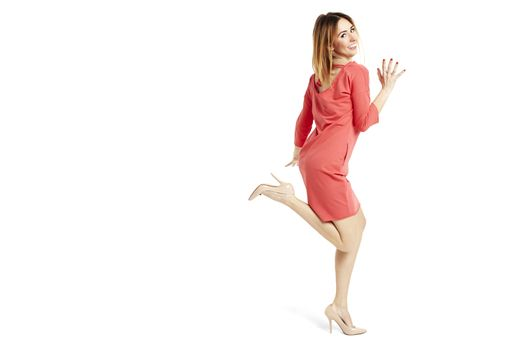 Side view of pretty woman in red dress running away.