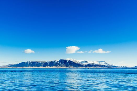 Blue ocean with distant mountains
