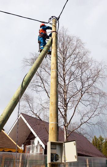 Electrician connects wires on a pole in a country house. Cottage