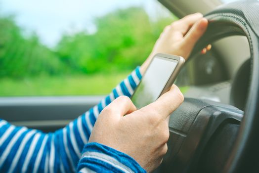 Female driving car and texting sms message on smartphone