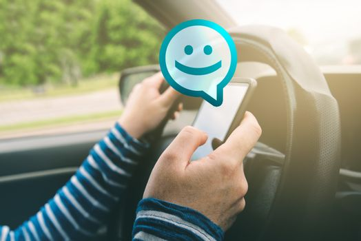 Female driving car and receiving smiley emoticon message on smar