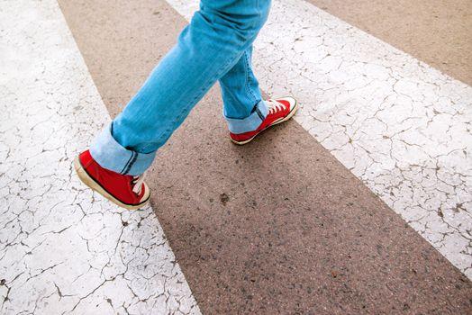 Young teenage person walking over pedestrian zebra crosswalk