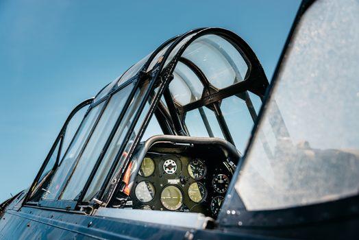 Open vintage airplane cockpit, blue sky background.