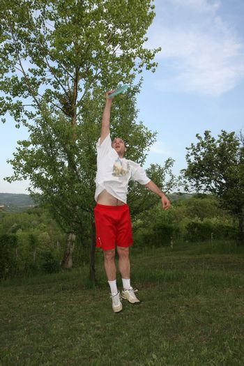 Young man in red and white playing fresbee in nature
