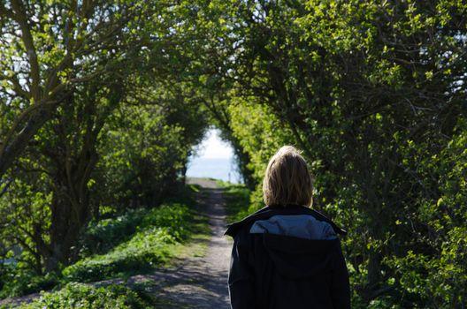 Woman walks in a green tunnel