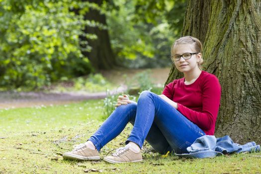 Young girl resting in park in spring day