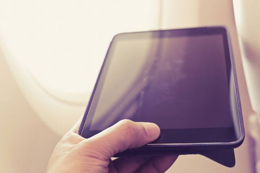 close up of business man siting near airplane window and using his digital tablet, Business communication
