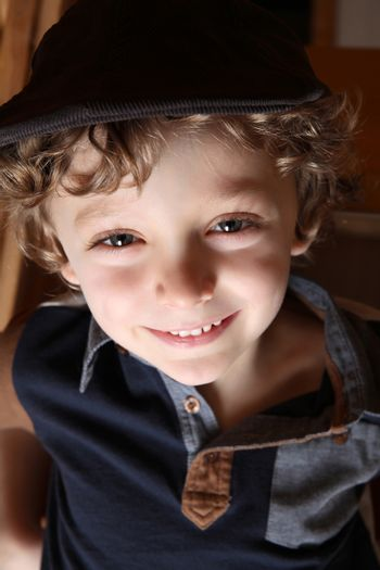 Young boy with curly blonde hair and blue shirt