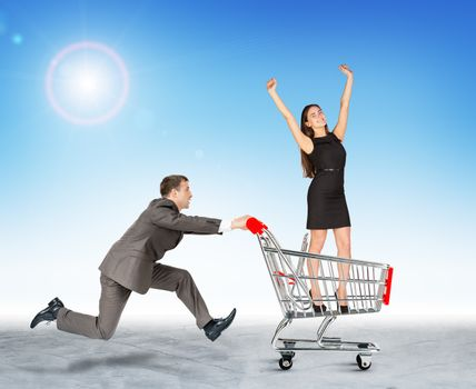 Running businessman with businesswoman in shopping cart
