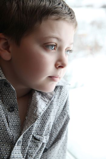 Young boy looking out of the window on a winters day