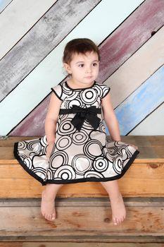 Brunette toddler girl against a colorful background