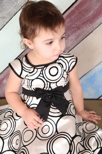 Beautiful brunette toddler girl against a striped background