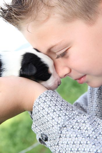 Young boy holding a week hold Border Collie puppy