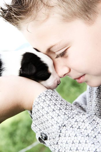 Young boy holding a week old Border Collie pup