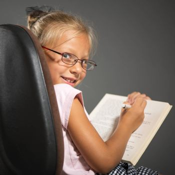 Cute little girl sitting and holding book. Studio shutting. Grey background. Looking at camera.