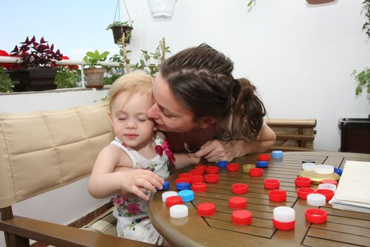 Mother interupting game of  her little girl by  kissing
