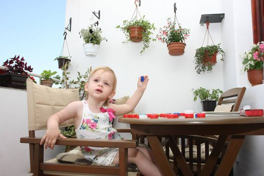 Young girl on terrace playing with bottle caps