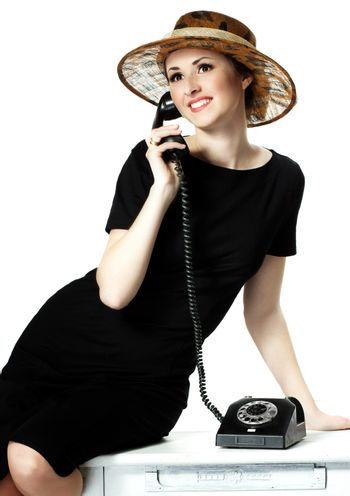 Portrait of a beautiful brown-eyed woman in a little black dress with a vintage telephone isolated on white background