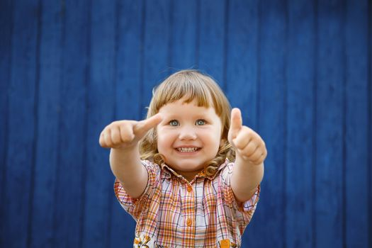 Portrait of happy joyful beautiful little girl against the old textured blue wall gesturing thumb