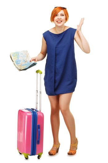 Full length portrait of a young woman standing with a pink suitcase and travel map gesticulating against white background