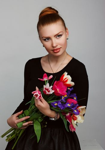Portrait of a beautiful red-haired girl with lush lips. A woman holding a large bouquet of colorful flowers.