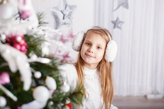 Beautiful little girl in earmuffs decorating Christmas tree with
