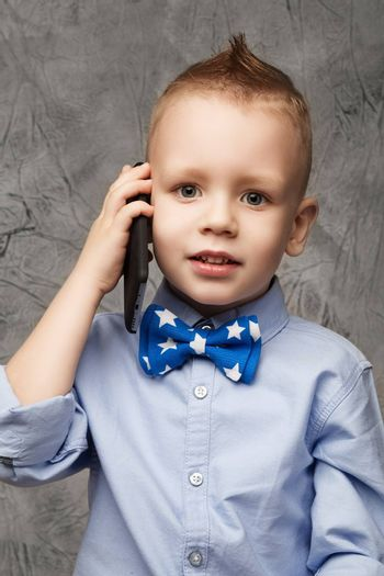 Portrait of a cute little boy in blue shirt and bow tie with mobile phone against gray textural background in studio.