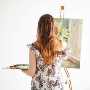 Woman Painting on a Canvas against white background. Back view.